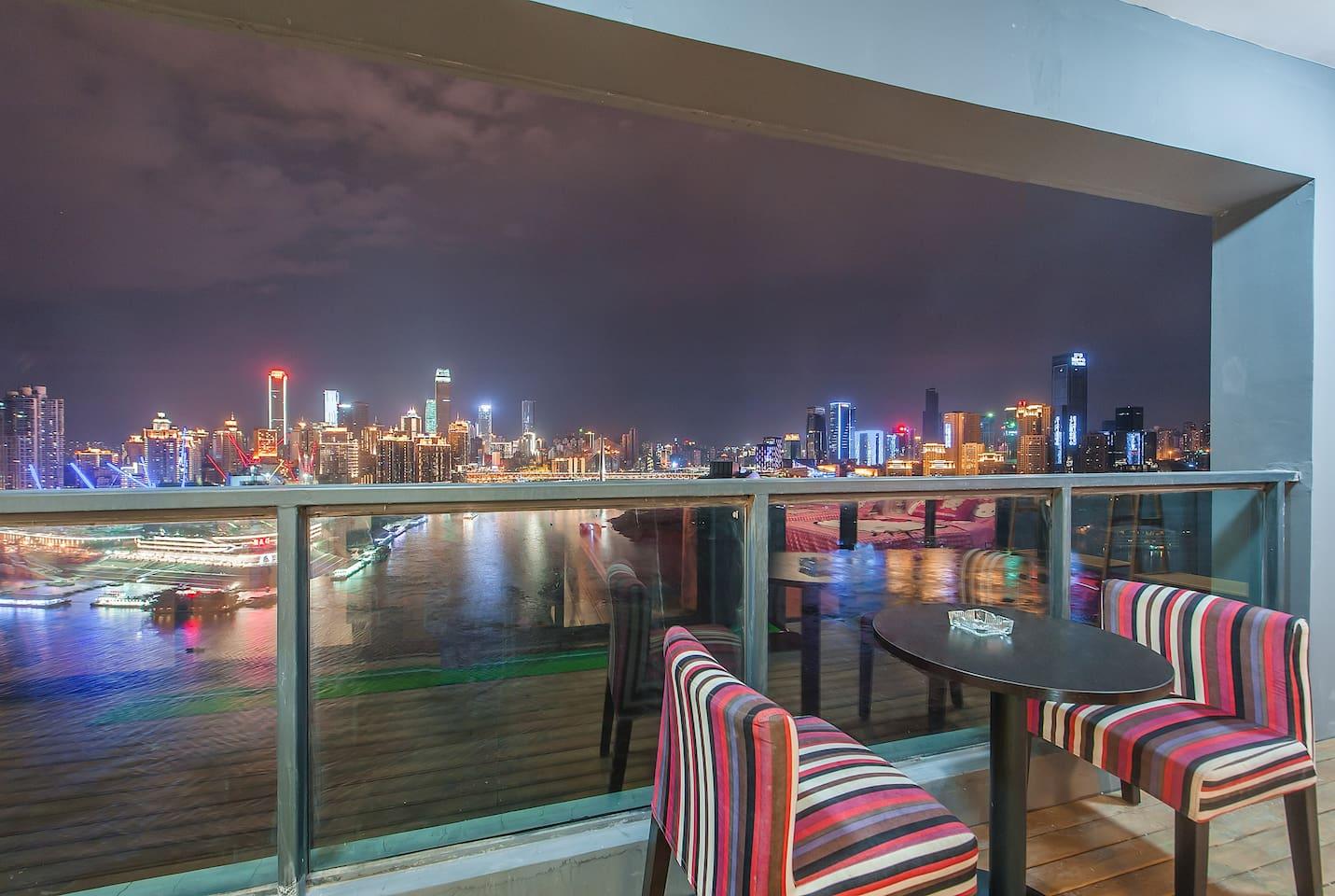 只有椅子、桌子、阳台这几样东西吗?不对还有对面的夜景和江景!