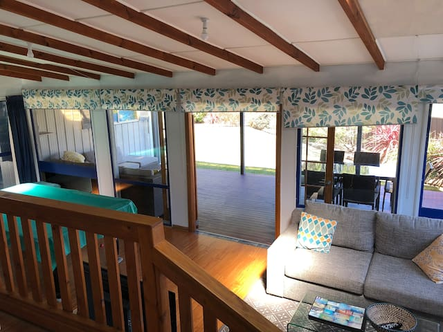 View from kitchen overlooking lower lounge, covered outdoor entertaining area and rear yard.