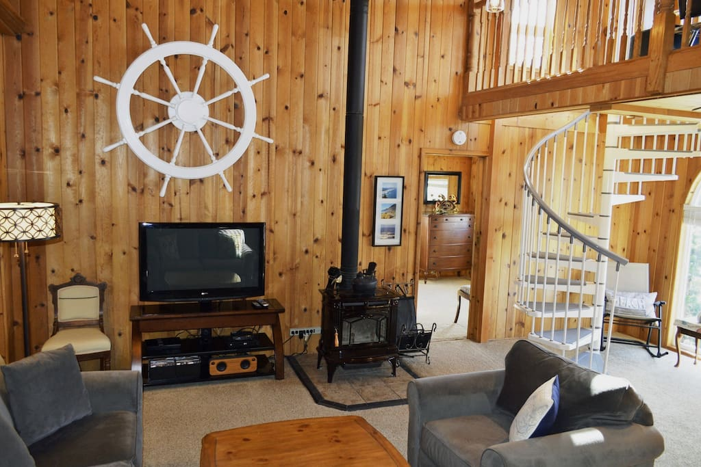 Open living room with a flat screen satellite TV/DVD player, Bluetooth speaker, glass front wood stove and spiral staircase to the loft.