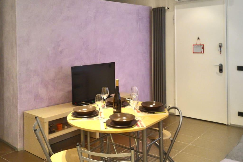 La zona giorno e tv led con tavolo da pranzo/ Living area with led tv and dining table