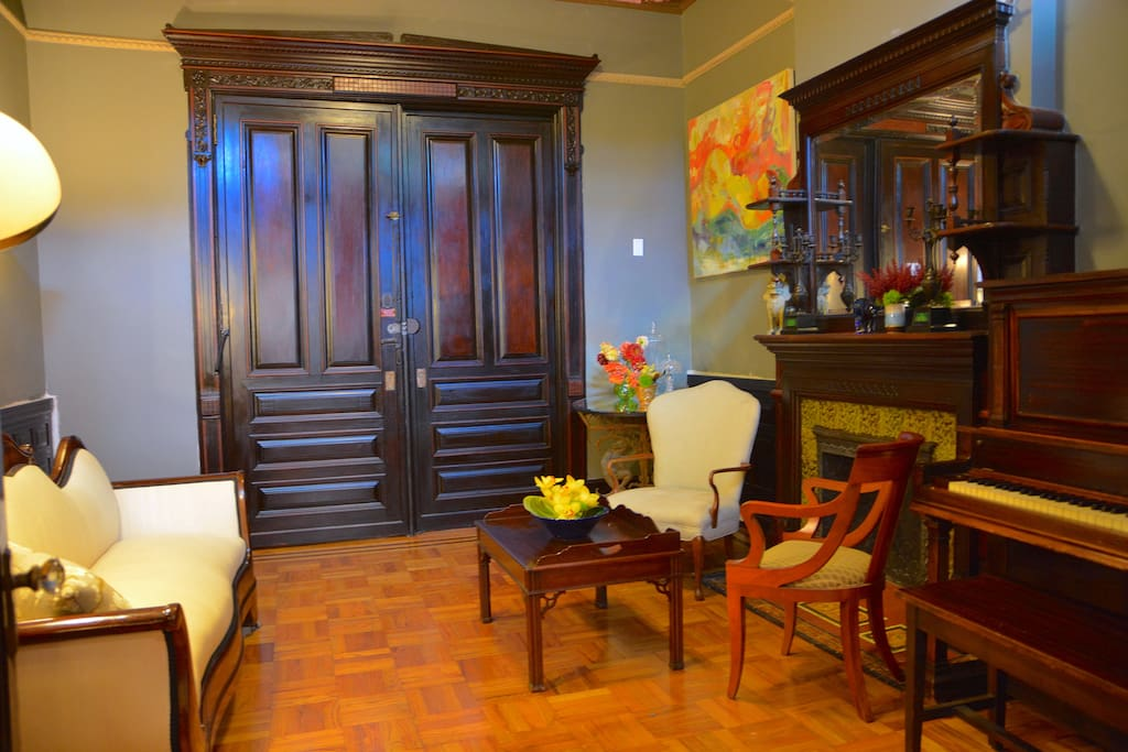 formal living room with Mahogany double entry doors, parquet original floor,   elegant fireplace and a vintage saloon piano for your intimate events.