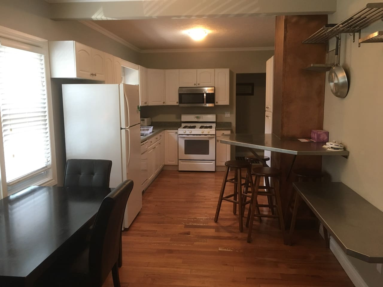 Open kitchen and eating area with table and raised bar