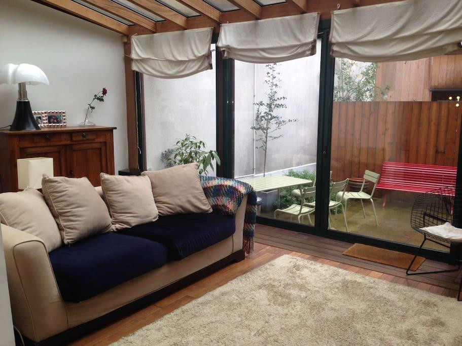le salon clair sous véranda donnant sur le jardin