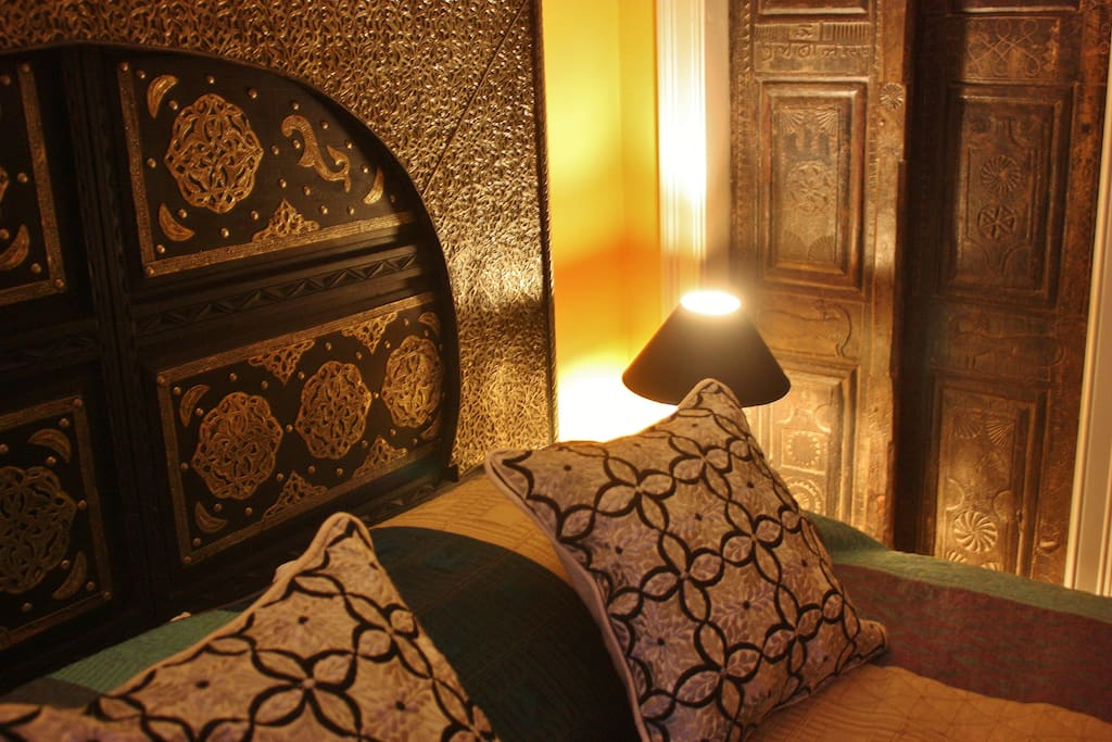 Moroccan carved cedar and silver bed, embroidered Marrakesh pillows. Antique Indian doors.