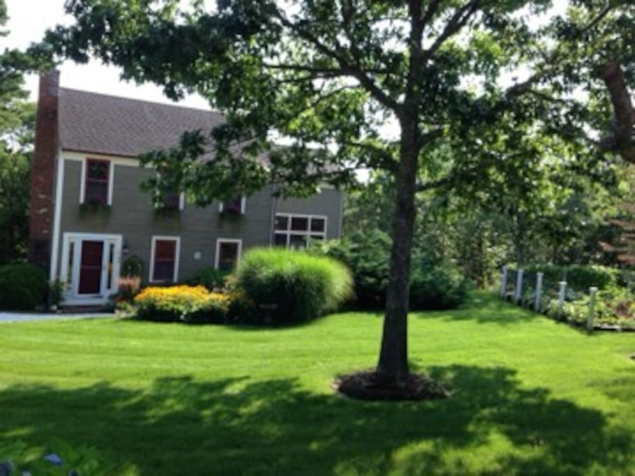 View of house. Flower garden in front with veggie garden to side. (Shell driveway not pictured)