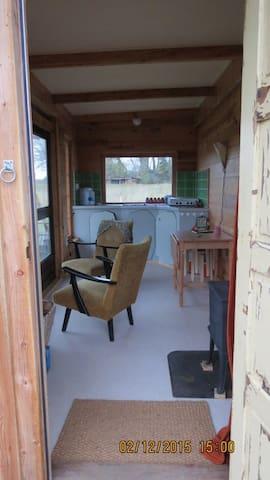 Woonkamer met op de achtergrond de keuken en op de voorgrond de houtkachel