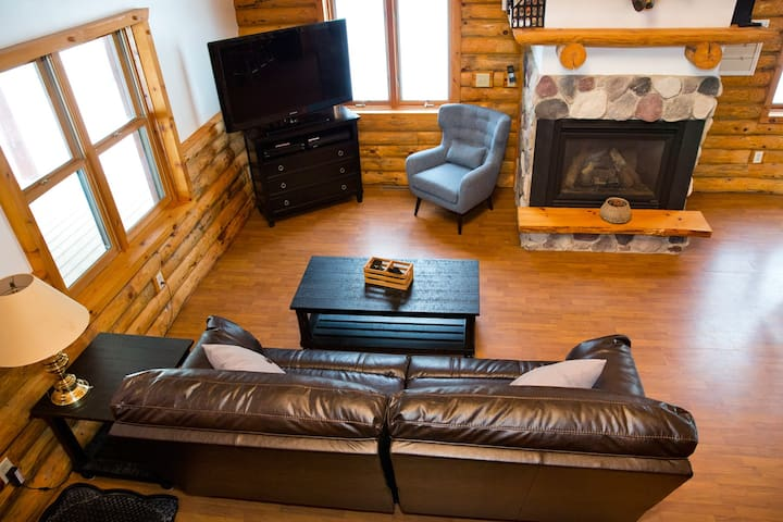 """Looking over living area from loft.  Enjoy a reclining leather couch great for naps. Watch satellite TV on a 52"""" big screen tv. A gas fireplace will keep you warm."""