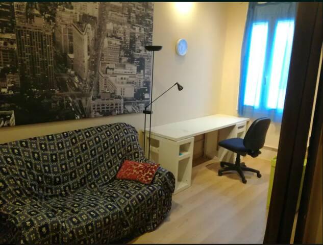 Habitación grande con mesa para trabajo y sofa