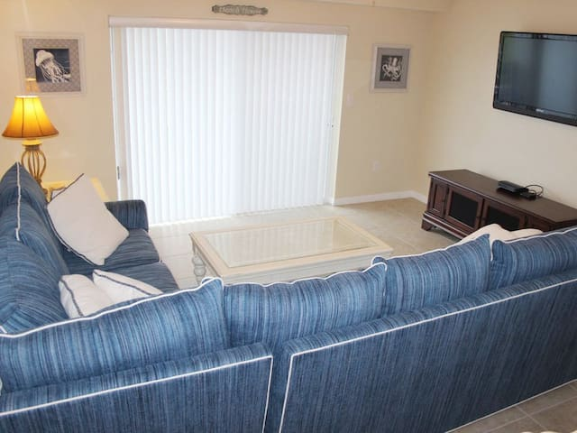 Spacious living room with wrap around couch, large flat screen TV and sliders to private patio.
