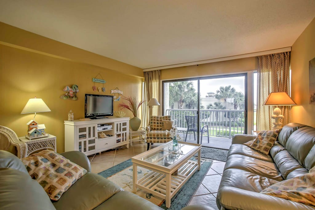 The spacious living room features plush furniture and has a sliding glass door.