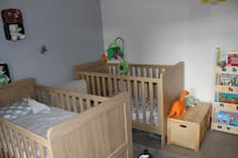 Children's bedroom contains two beds, toy box and bookshelf.