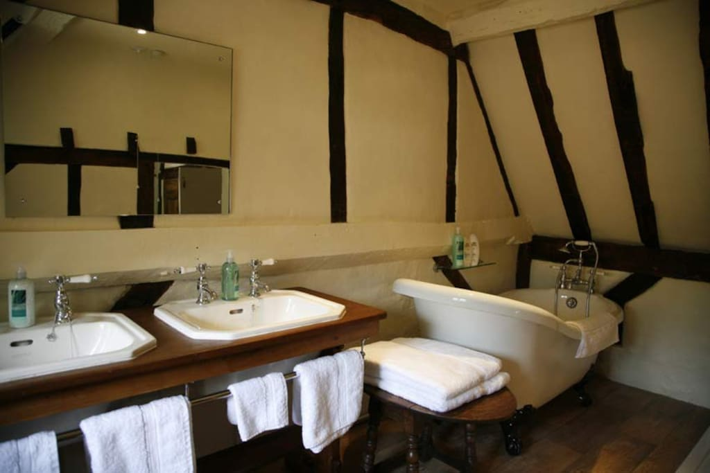The bathroom for the master bedroom, with twin basins, roll-top slipper bath and a glass shower