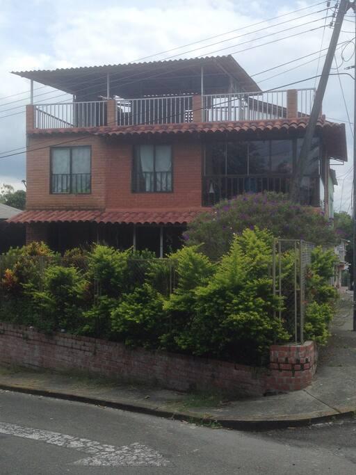 Vista frontal de la casa y jardín.
