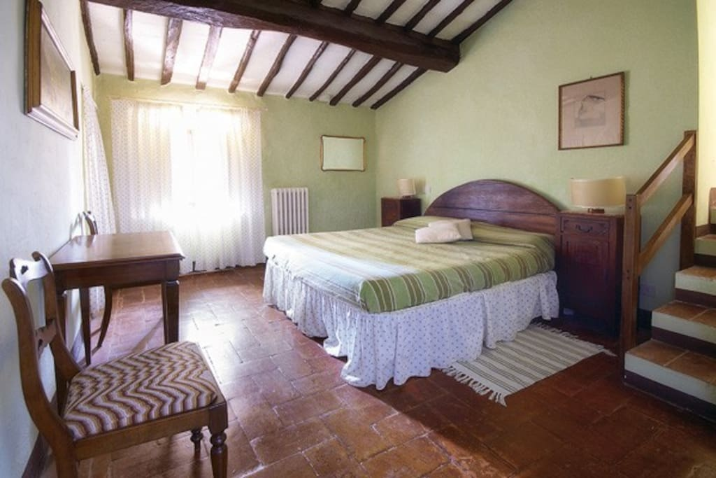 Green en-suite bedroom with sunset desk and original beamed ceilings
