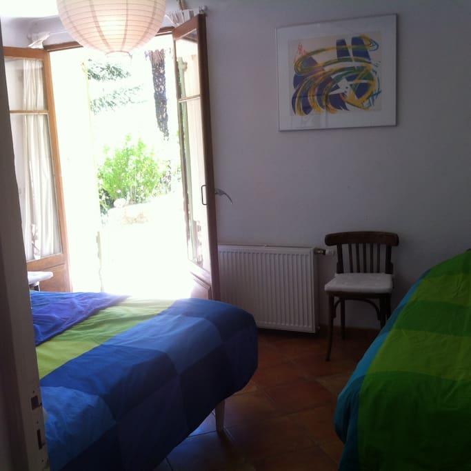 Slaapkamer met openslaande deuren naar de tuin