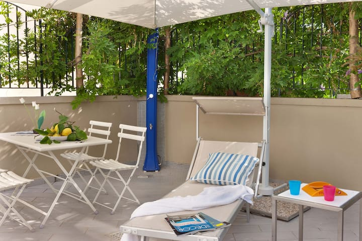 Patio with garden furniture, shower and barbecue.