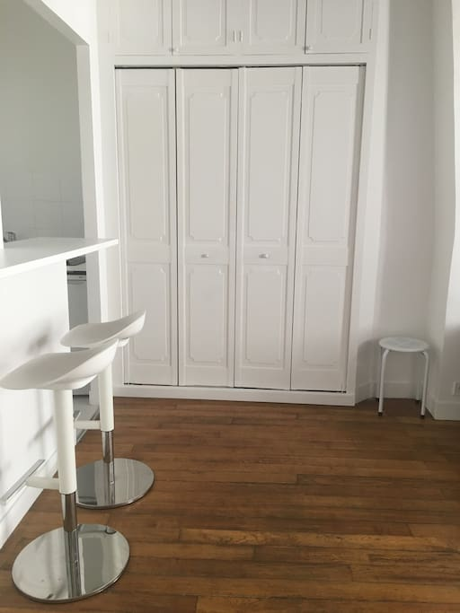 Small kitchen with bar table and stools. Inside wardrobe