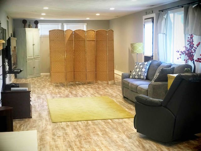 Spacious daylight living room with second bedroom featuring custom made log bed, at the end