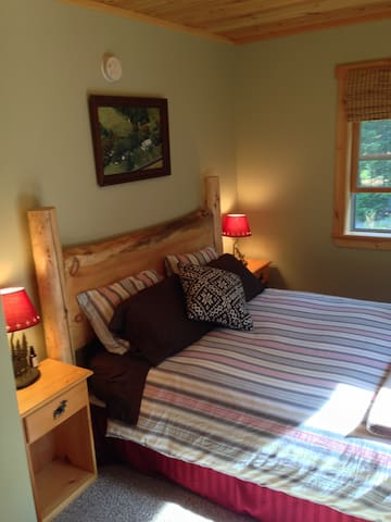 Main floor 1st bedroom with queen bed and forest views.