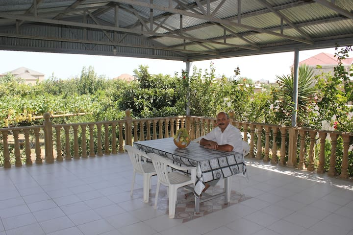 Panoramic balcony surrounded with green trees and flowers. This area is better  for relaxing and tea break. I like to sit here with my guest during dinner time & treat them home made wine or chacha, seasonal fruits from my garden.