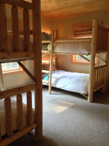 Main floor 2nd bedroom with 4 twin bunk beds and forest views.