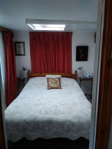 The bedroom with double bed and bedside tables with lamps and alarm clock.   Be woken up by either the buzzer or the sunshine function on the clock.
