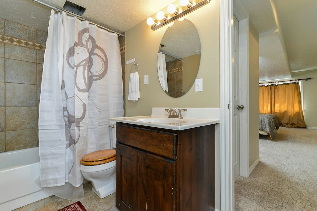 Shared full bathroom with tile floor and tub surround, vanity and sink