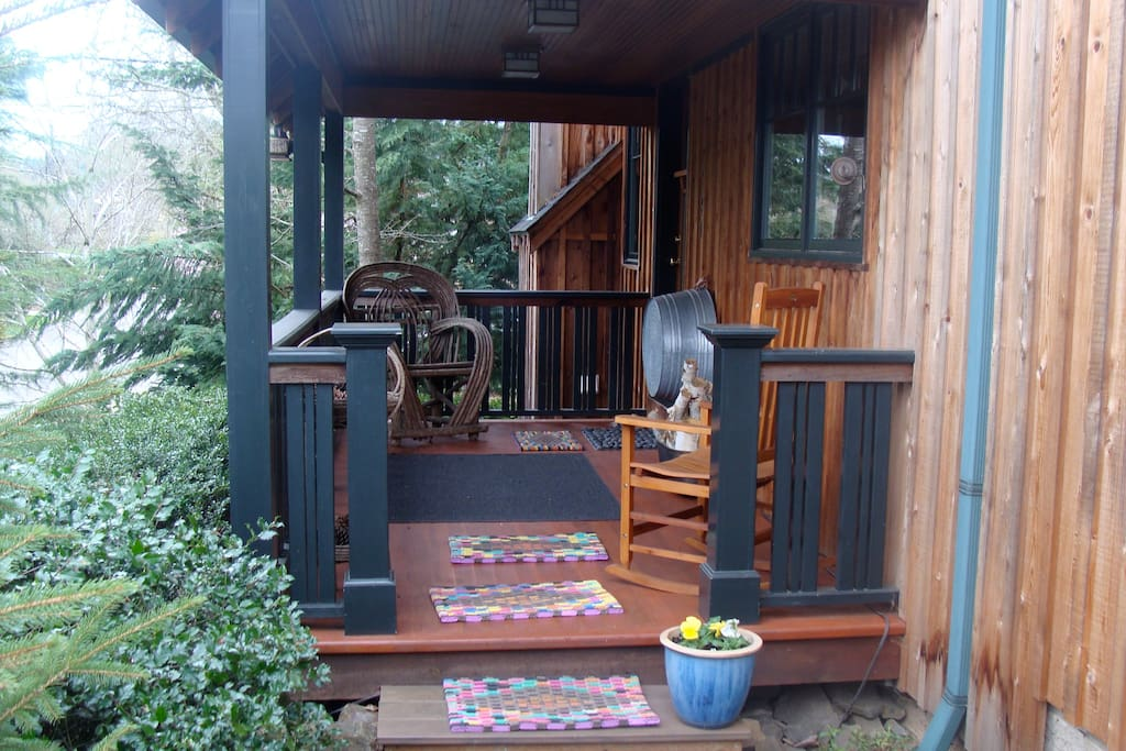 Cozy front porch faces private, wooded garden