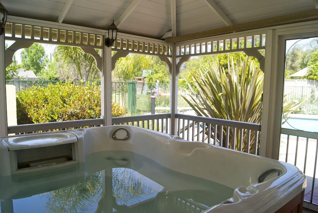 The hot tub is inside of a screened in gazebo.