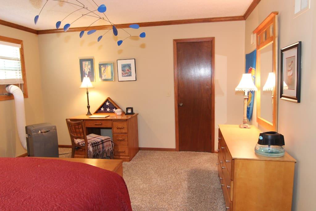 Room with desk facing walk-in closet