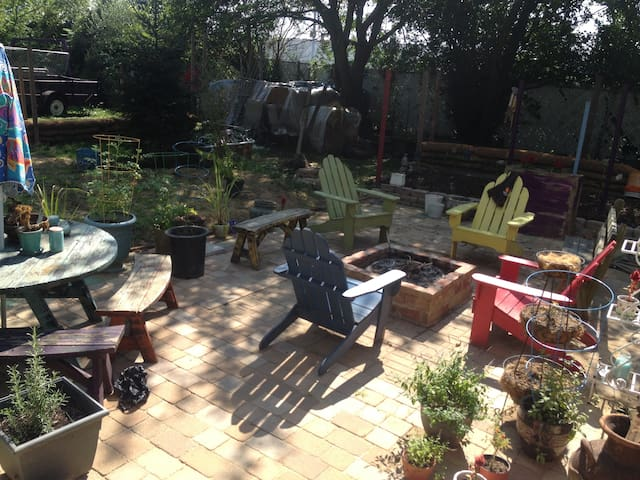 Backyard patio with dining table and fire pit... Great for day and night use