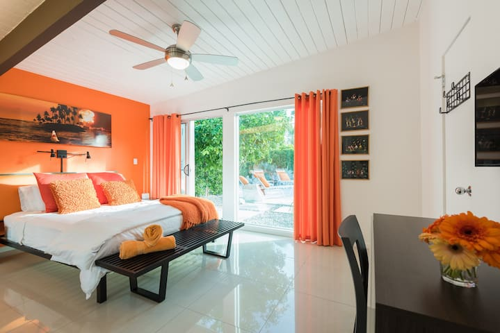 """The orange bedroom.   The """"Master"""" bedroom of the main house. Queen size bed, en-suite bath and direct pool access and views."""