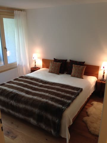 Large bedroom with double bed, 2 bedside lights & small terrace.
