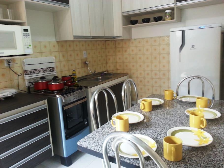 Cozinha modulada com fogão, geladeira, mesas, cadeiras, panelas, microondas, sanduicheira, cafeteira, liquidificador, pratos, copos, xícara e talheres