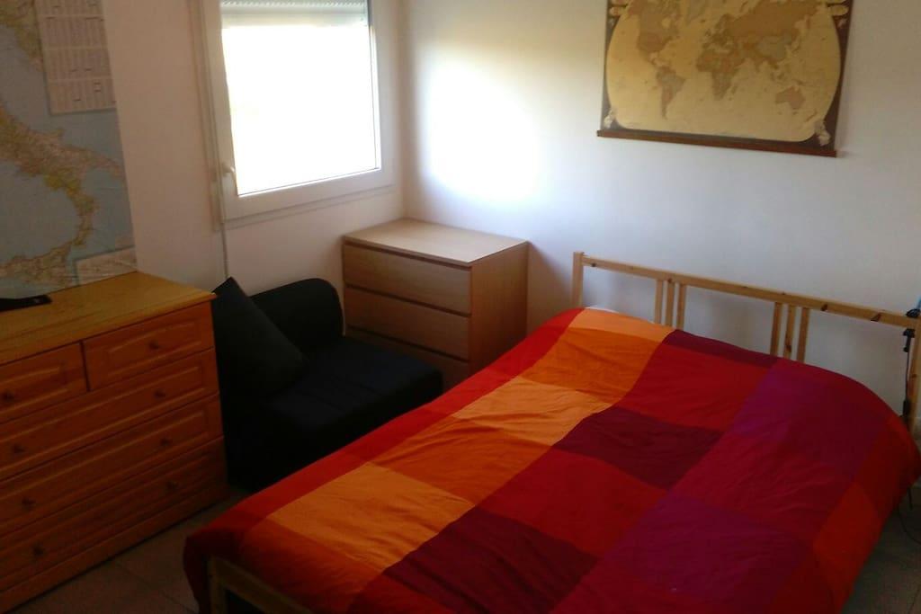 Chambre avec grand lit et un canapé-lit