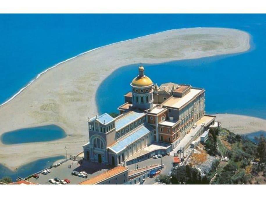 santuario della Madonna nera del Tindari con la lingua di sabbia dorata e i famosi laghetti di marinello .Santuario della Madonna nera