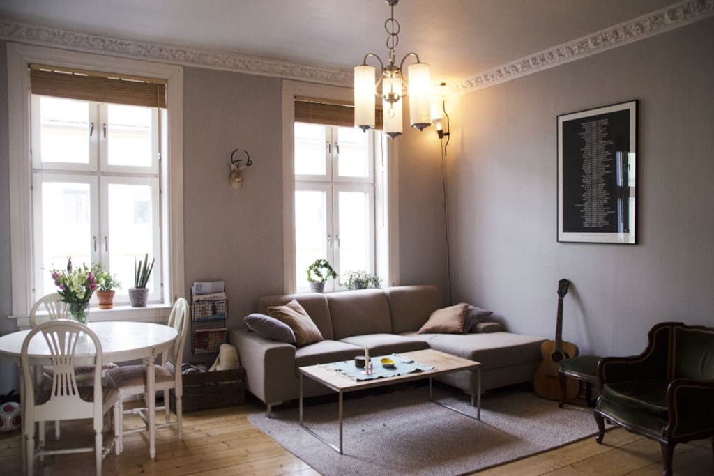 Living room is spacious and light. There is a lounch area with a tv and a fireplace as well as a small dining table.