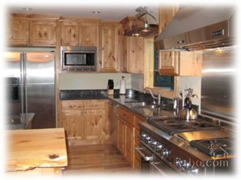 Chef's kitchen with stainless appliances, granite countertops and island with seating for 4