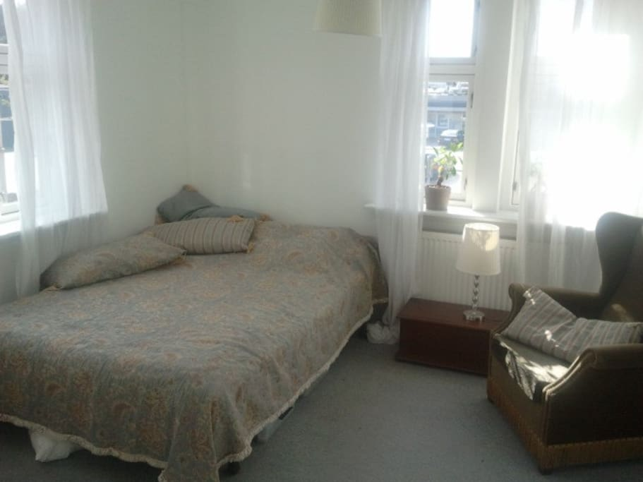 The room has natural light from two sets of windows and a nice double bed.