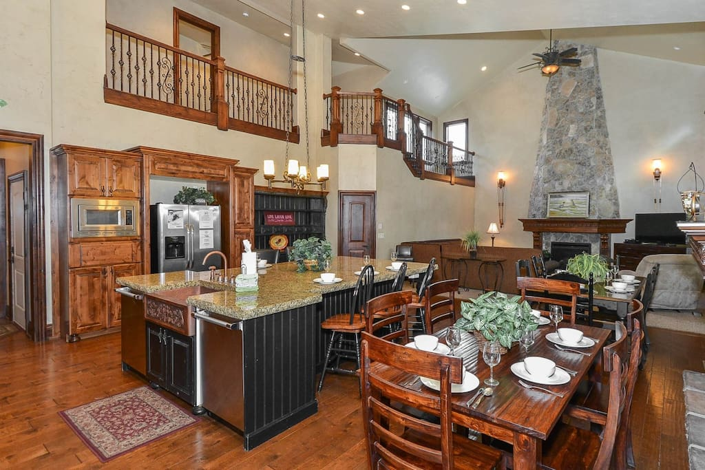 Large gourmet kitchen with Viking range and farm sink with huge island with bar seating and two dining tables