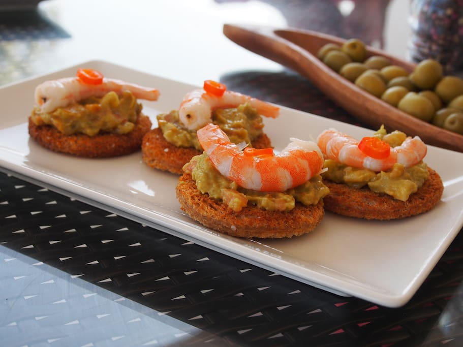 Tostadas topped with guacamole and prawns