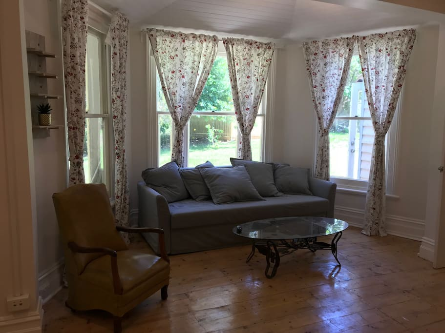 a living room with provincial widows facing private garden