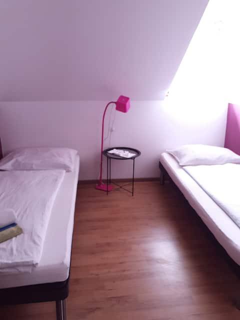 Kleine kamer met 2 bedden en gedeelde badkamer