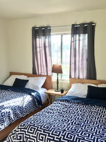 Habitación con dos camas matrimoniales, aire acondicionado, espejo, armario y maletero.