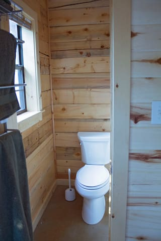 Toilet is located inside the cabin, while the shower is outdoors.