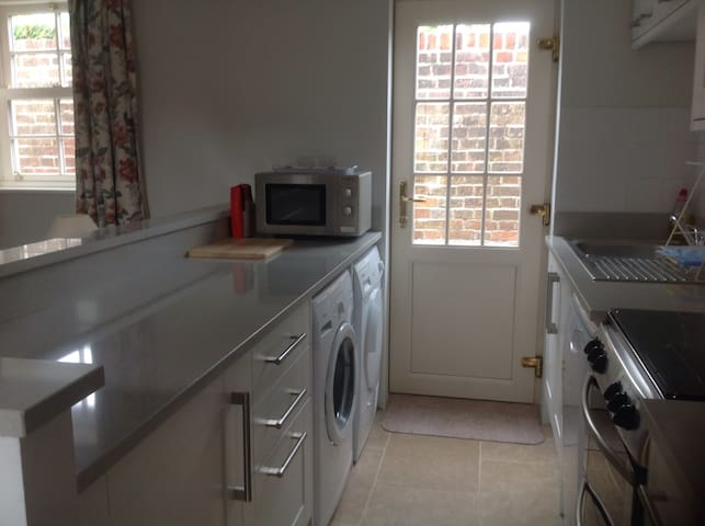 Fully equipped open plan kitchen with washing machine, dishwasher, microwave, dryer, full sized oven and gas hob