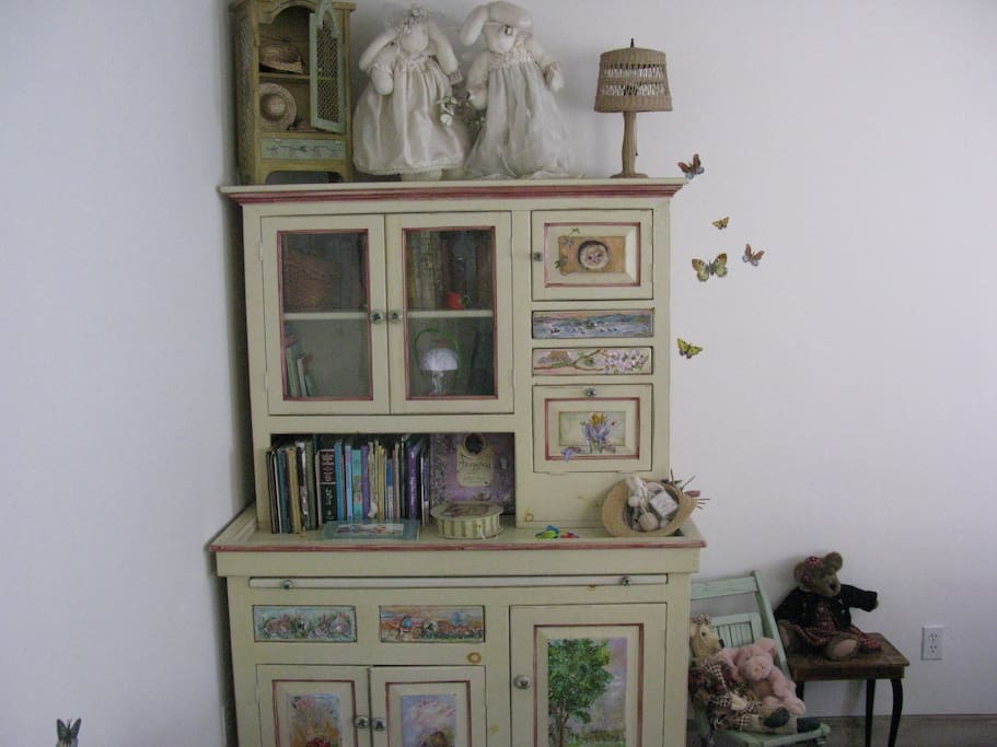 Hand painted hutch filled with children's books, new and antique, for your use and enjoyment. Also a closet full of toys and Disney movies can keep children happy.