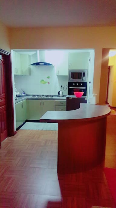 It's an open kitchen. On the right is the Inbuilt microwave,Oven and cupboards.Infront  of it is the kitchen Refrigerator.  Electric Kettle on its left.