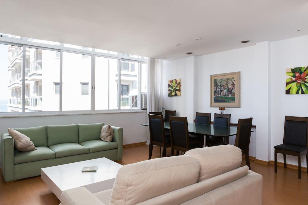 Sala com sofás de 2 e 3 lugares, mesa com 8 cadeiras , TV  a cabo e ar condicionado.