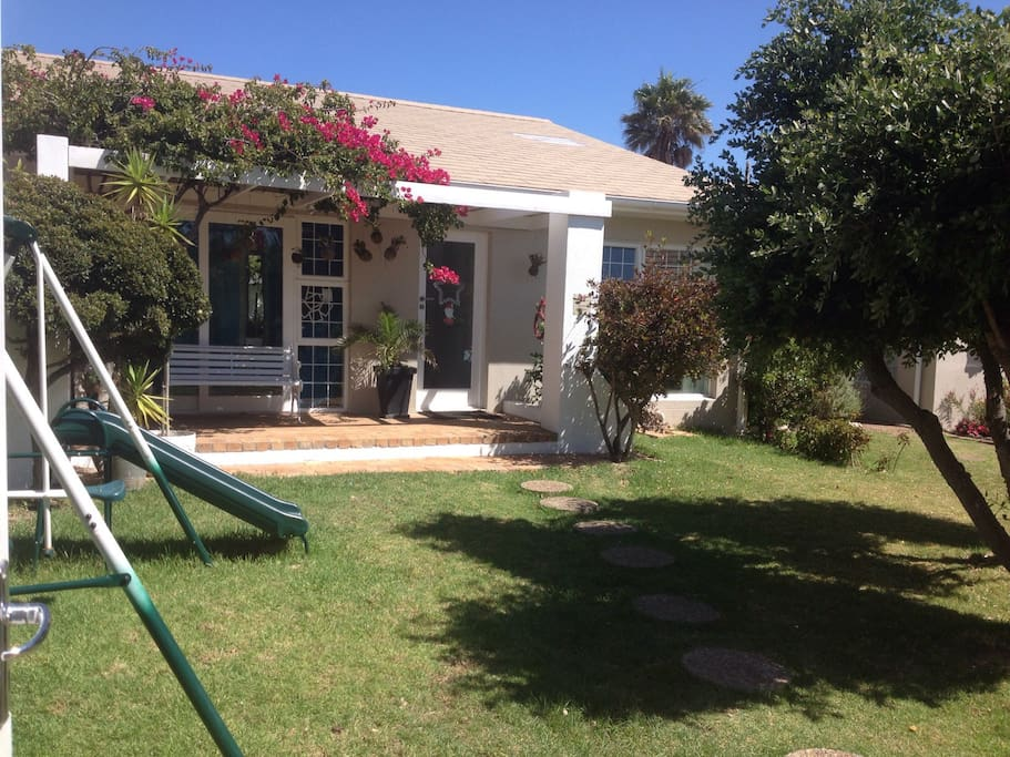 Front yard, entrance to the house, swings and beautiful pink Bougainville